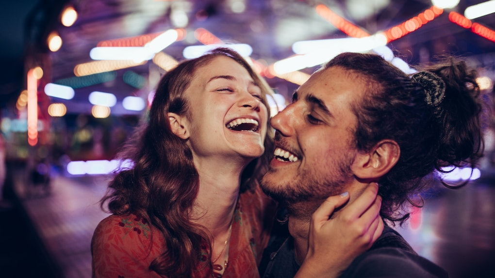 A happy couple laughs in an amusement park on a date at night with lights faded in the background.