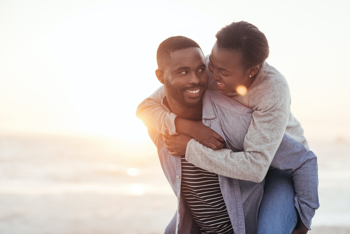 Young African man giving his laughing girlfriend a piggyback while enjoying a late afternoon together at the beach