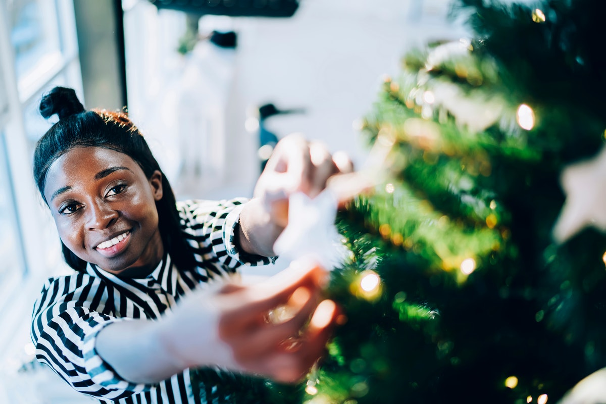 A woman smiles as she looks up and hangs an ornament on her Christmas tree in her home.