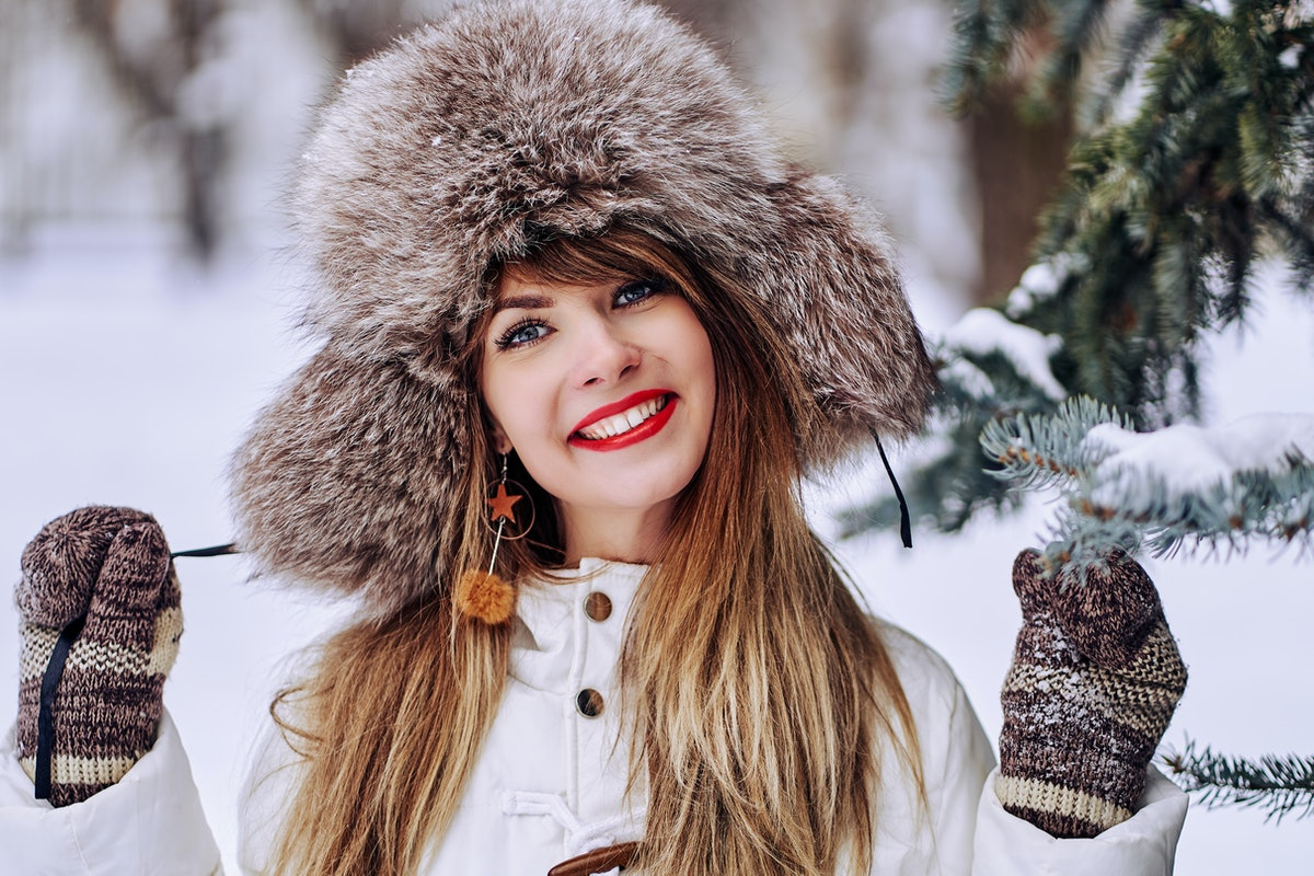 A brunette woman wearing mittens and a matching hat smiles next to an evergreen tree in winter.