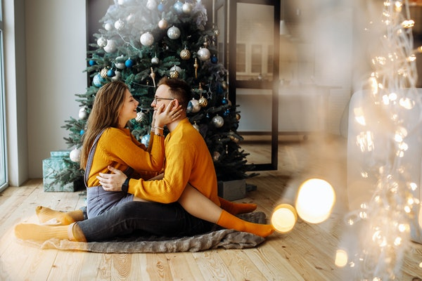 A happy couple dressed in matching yellow sweaters looks at each other and sits on the floor next to their Christmas tree.