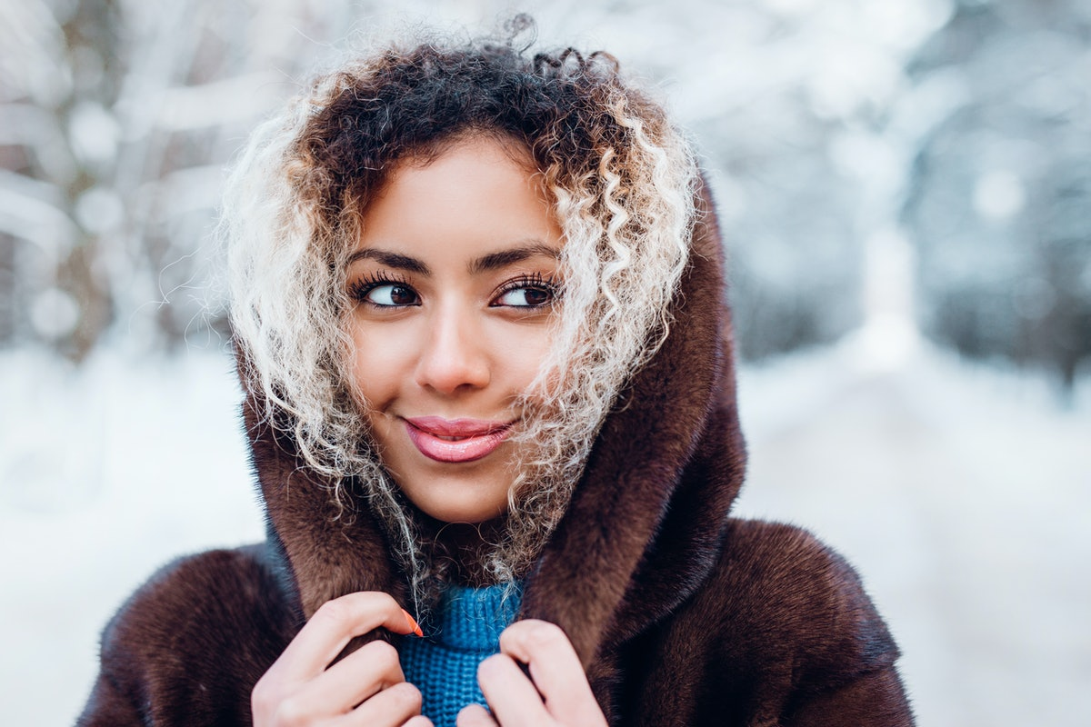A woman smiles and looks to the side while she holds her hood up outside with snow in the background...