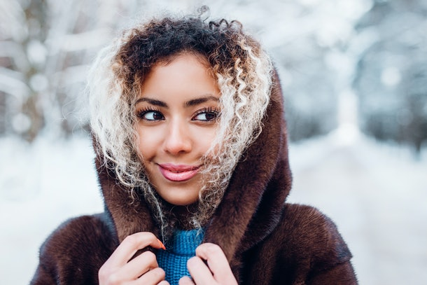 A woman smiles and looks to the side while she holds her hood up outside with snow in the background.