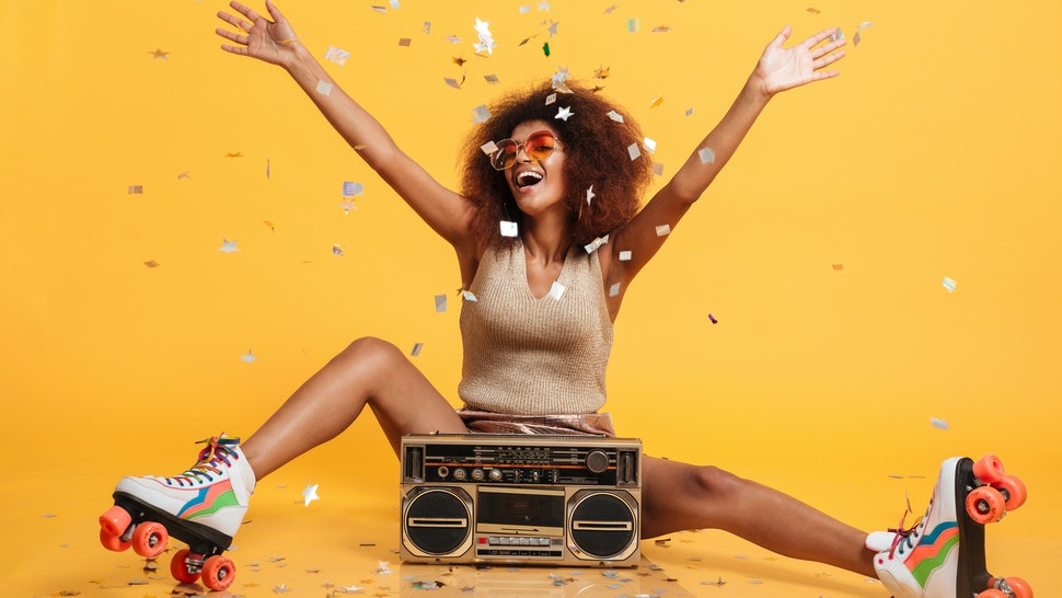 Charming young african woman in retro wear and roller scates throwing confetti while sitting with boombox, isolated on yellow background