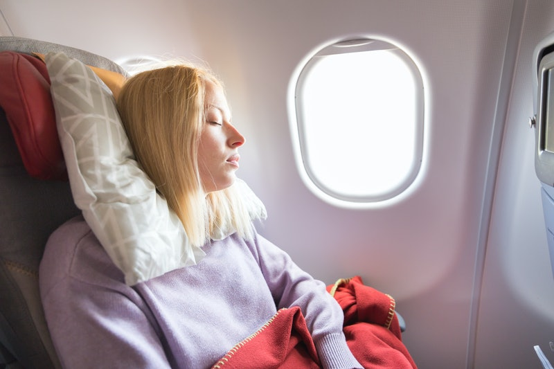 Tired blonde casual caucasian woman sleeping on seat while traveling by airplane on long distance tr...