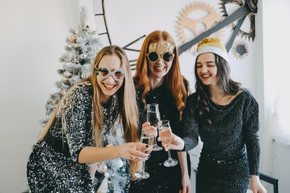 Cheers! New Year Eve, Christmas Celebration. Three partying girls clinking flutes with champagne. Yo...