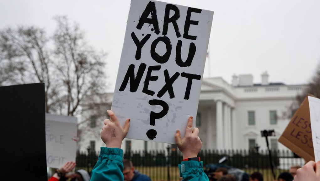 Demonstrators hold signs during a protest in favor of gun control reform in front of the White House, in Washington