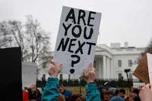 Demonstrators hold signs during a protest in favor of gun control reform in front of the White House...