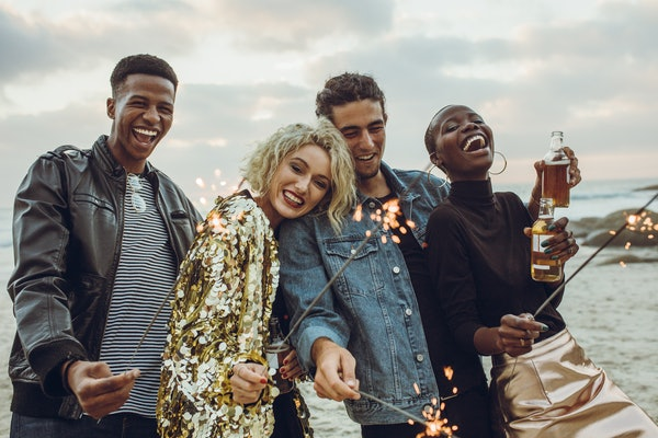 A group of friends in sparkly and stylish clothes holds sparklers and bottles of beer while celebrating New Year's Eve on a pier.