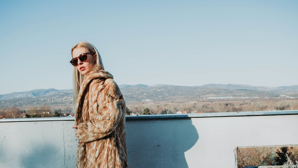 A blonde woman in a long coat and sunglasses stands on a balcony overlooking an underrated wintry town.