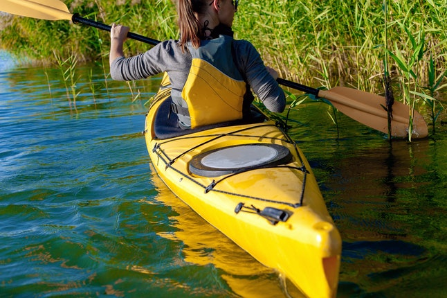 woman on kayak swims through the jungle.reed on the river