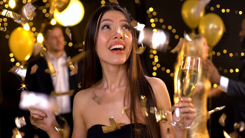 Positive woman holding champagne glass and sparkler, confetti falling down