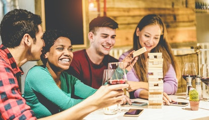 Young friends playing board games at hostel living room - Diverse culture people having fun and drinking wine at pub restaurant - Friendship and alternative evenings concept - Focus on afro girl face