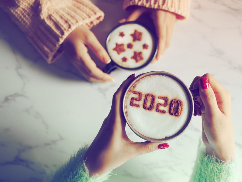 Coffee cup with the number 2020 on frothy surface in female hands holding over blurred marble table background and another one with star symbols on frothy surface. Happy new year 2020 food art theme.