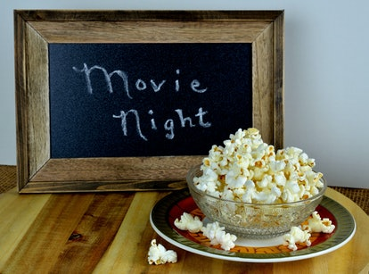 Freshly popped hot buttered homemade popcorn served in a bowl.  A sign suggesting movie night in the background.