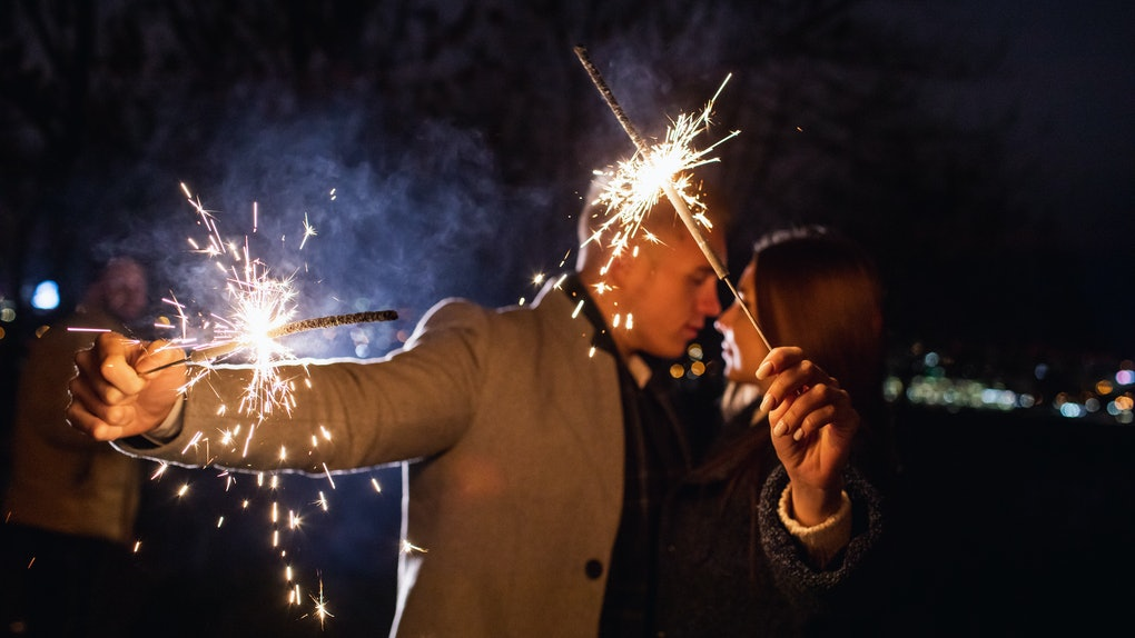 Romantic couple in love celebrate together the new year start or event party nightlife with fire sparkler