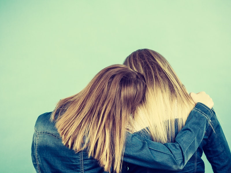 Back view of two unrecognizable blonde women hugging each other. Friendship, family love concept.