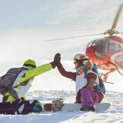 pair of freeriders of snowboarders give five when the helicopter lands