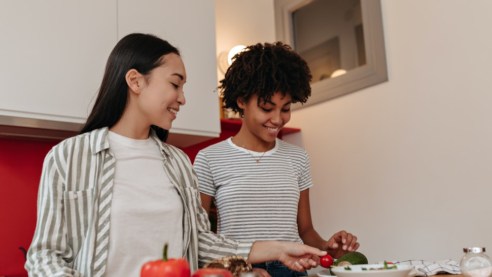 Portrait of brunette girls during cooking and cutting vegetables for diet dinner