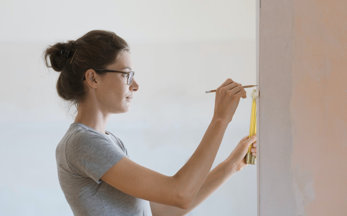Young woman doing a house renovation and measuring walls with a folding ruler, DIY and home makeover concept