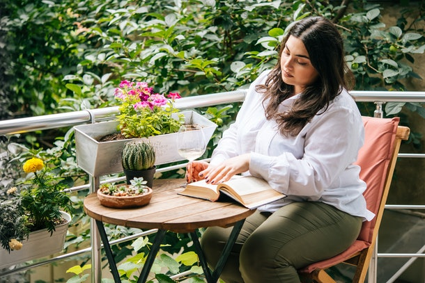 Portrait of beautiful plus size girl reading a book on balcony or terrace of cafe