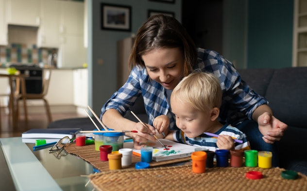 Positive female babysitter in casual clothing helping with painting to small blond haired boy sitting on couch at living room at home