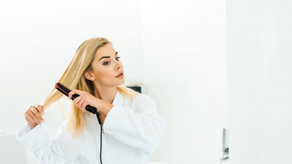 beautiful and blonde woman in white bathrobe using flat iron in bathroom