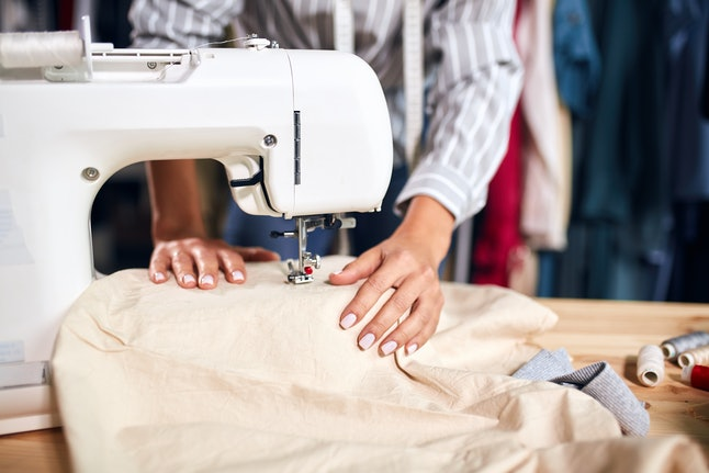 close up cropped photo.hardworking talented creative tailor mending cusstomer's clothing. working process.