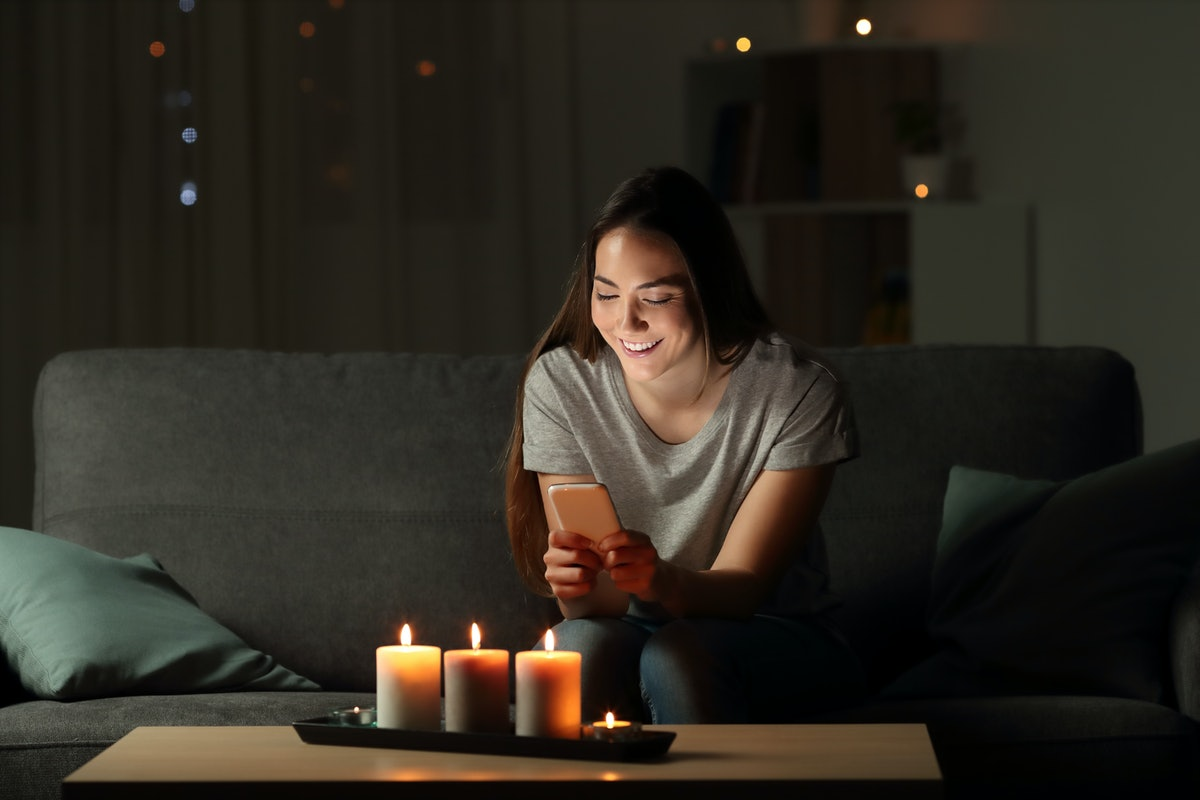 Woman using a smart phone in the night with candle lights sitting on a couch in the living room at home