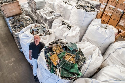 On, founder of the company, Out Of Use, Mark Adriaenssens, stands among bags of electronic parts and...