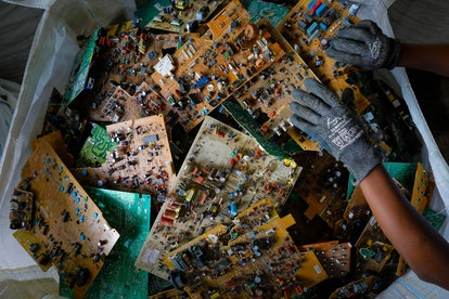 A worker picks up a motherboard seen in a basket before being shipped to Europe for safe processing ...