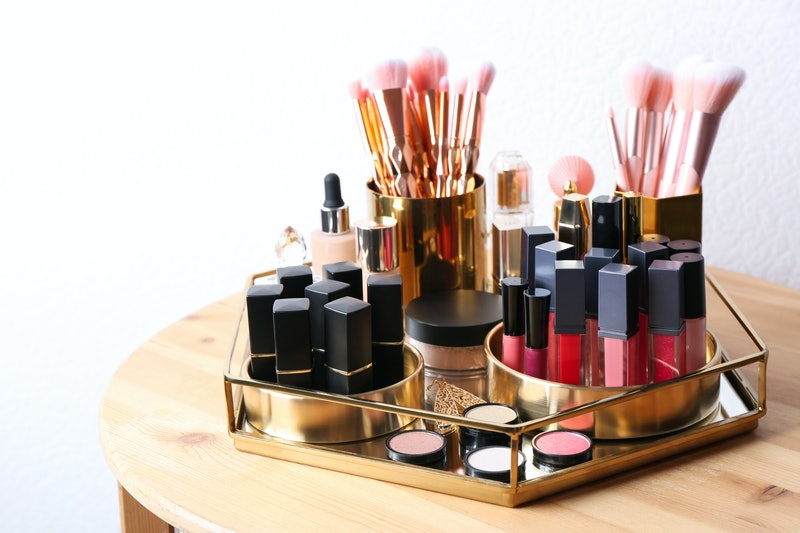 Set of luxury makeup products and perfume on wooden dressing table