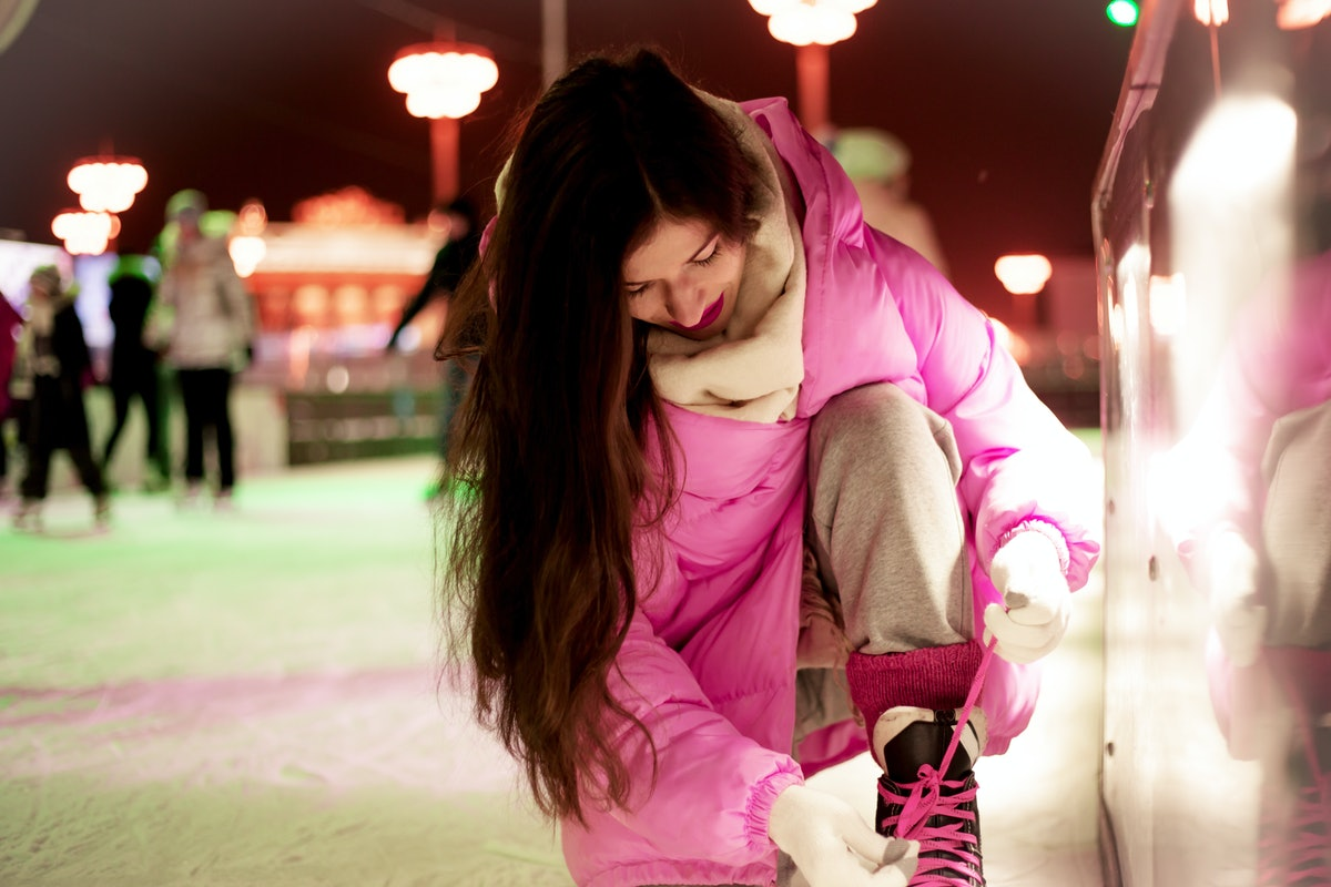A woman in a bright pink jacket ties her ice skates while skating at a rooftop ice skating rink.