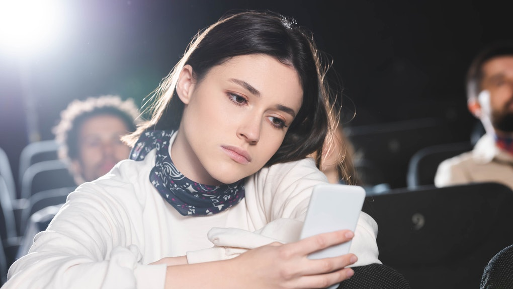 selective focus of sad woman using smartphone in cinema