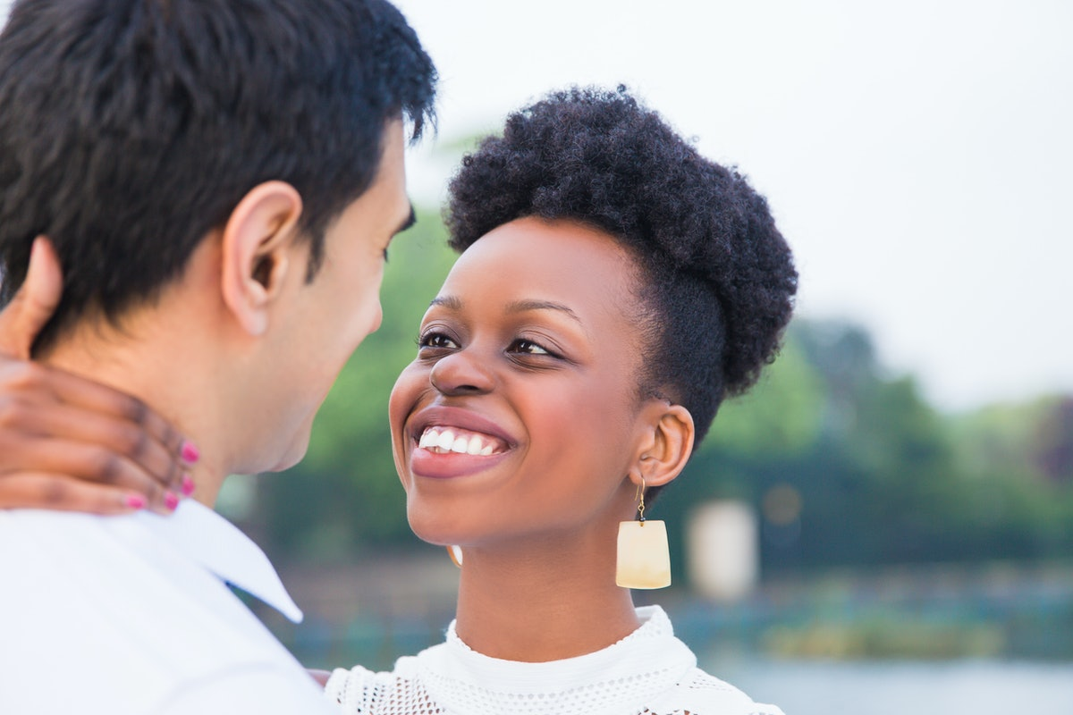 Close-up the young romantic smiling couple standing in embrace face to face in the park