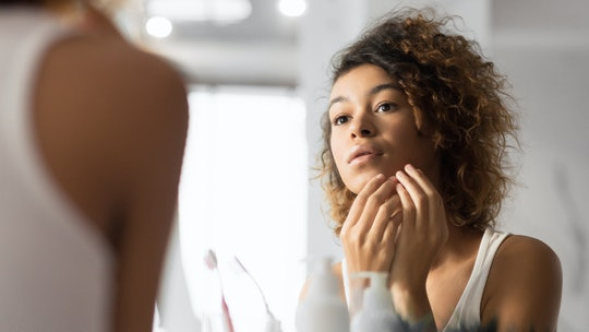 young woman looking at her face in the mirror