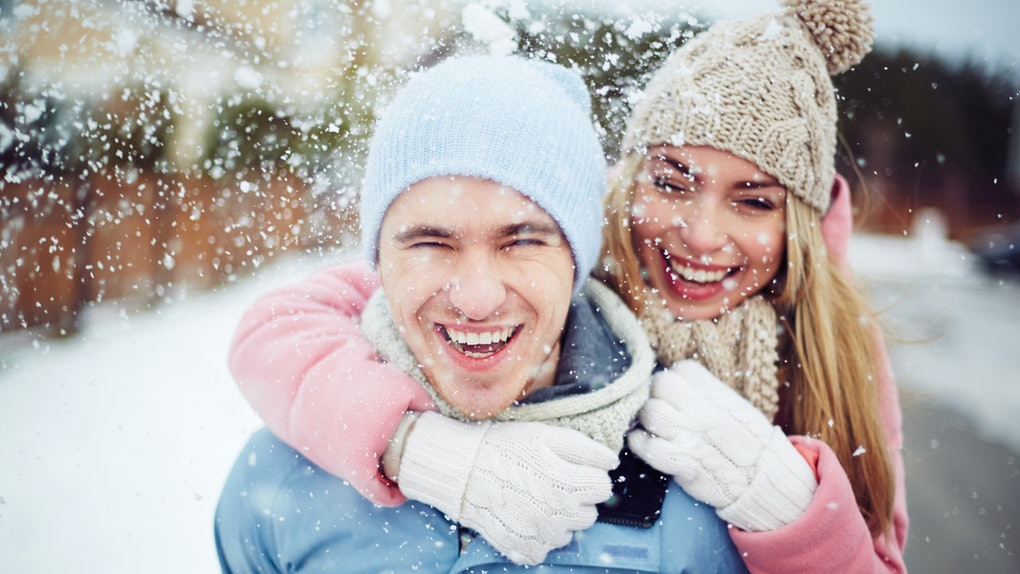 A happy couple laughs in winter coats and hats while it snows outside.