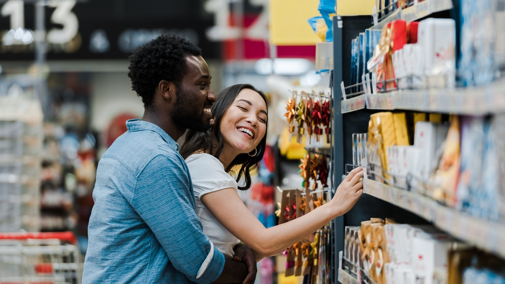 selective focus of cheerful african american man standing with asian woman smiling near groceries in supermarket