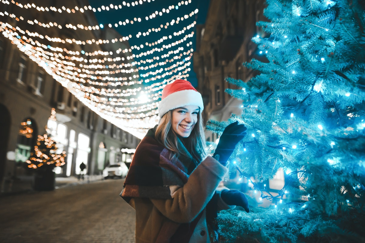 A woman wearing a Santa hat and pea coat smiles next to a Christmas tree outside in the winter.