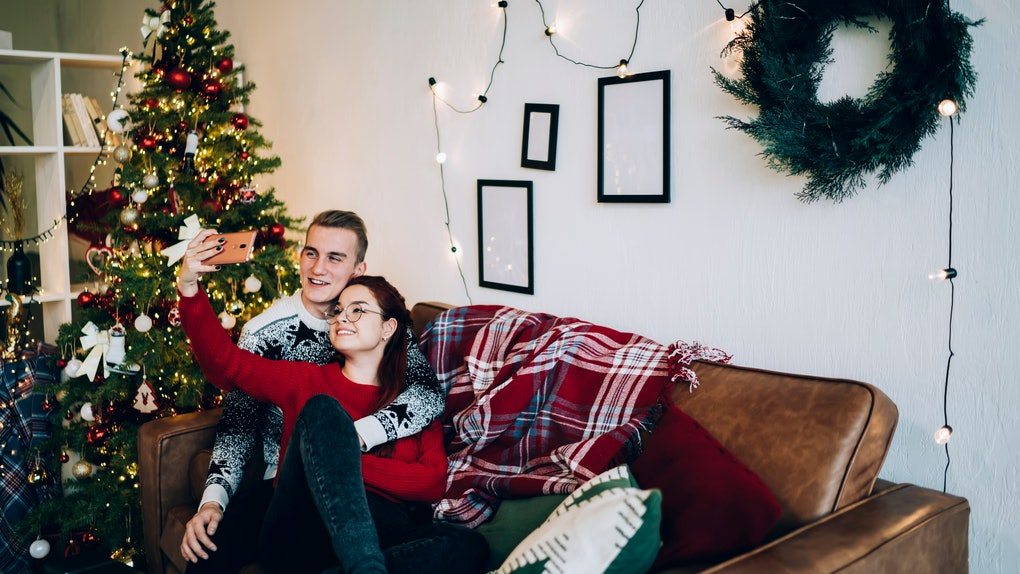 A couple wearing holiday sweaters smiles and cuddles on the couch next to a Christmas tree while taking a selfie.