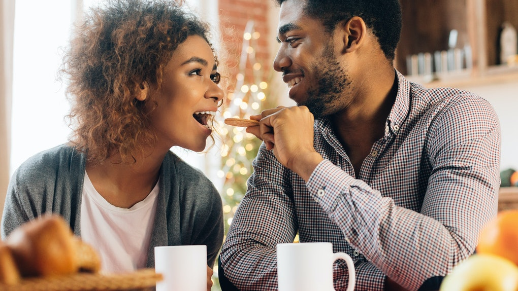 A happy couple sits at a kitchen table with coffee mugs, while one feeds the other a cookie.