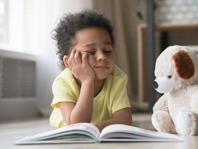 little boy reading a book with his teddy bear