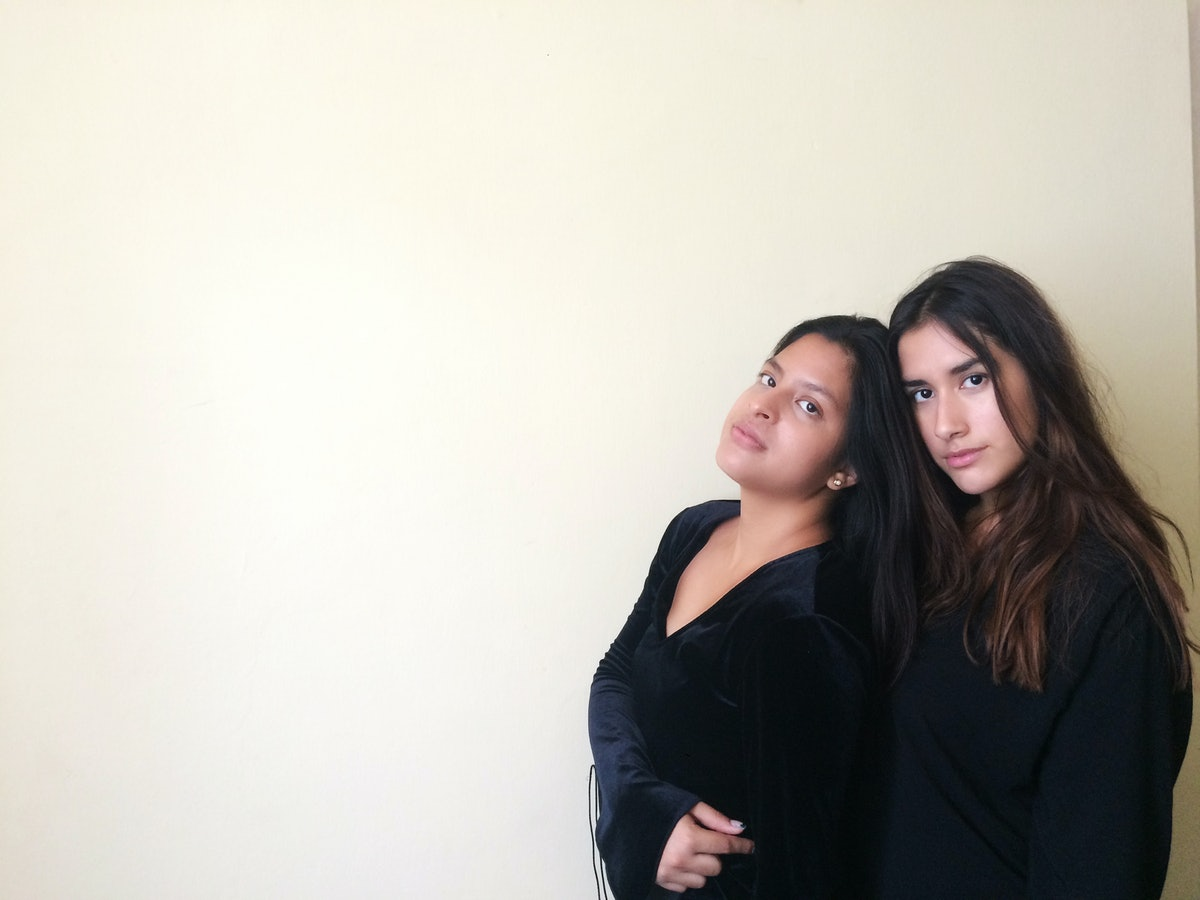 Two pretty friends women with long hair wearing black clothes in soft background. Girls together in soft yellow background.