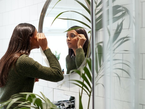 Businesswoman At Home Putting On Make Up In Mirror Before Leaving For Work