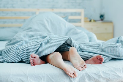 Feet of lovers couple lying on bed under blanket
