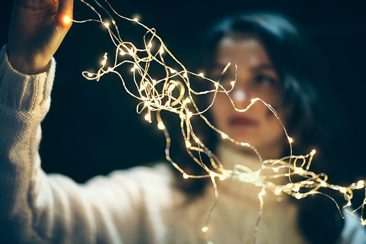 Beautiful woman hanging christmas lights. Holiday concept