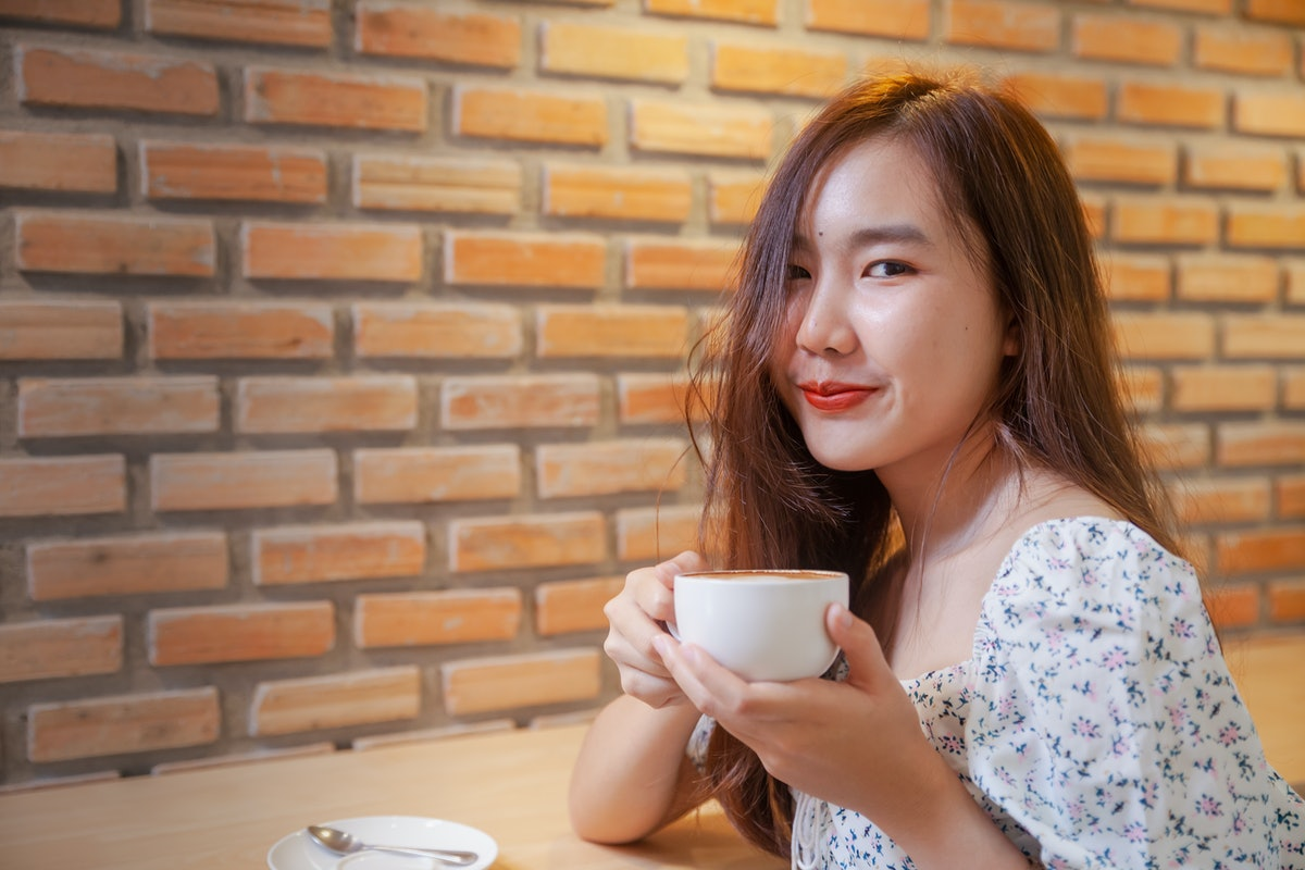 Asian women relax with hot coffee latte art with empty space .
