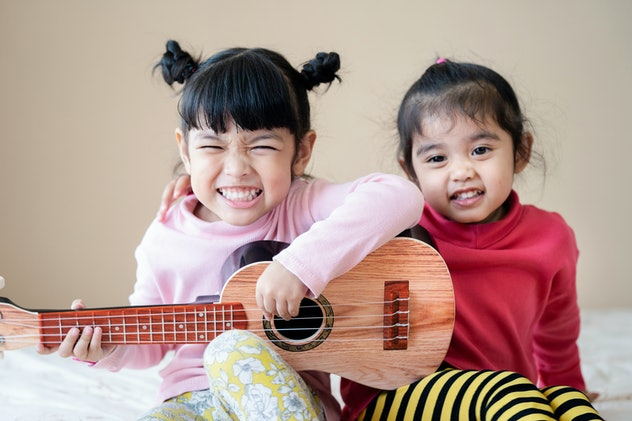 Kids playing guitar and singing the song of music together at home.