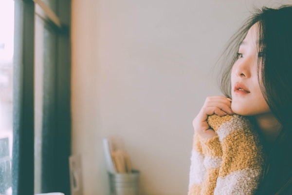 Beautiful young girl Black hair, yellow sweater sitting alone sad at home look out window sad Winter spring concept after grieving from love.