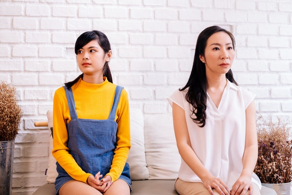 Unhappy mother and daughter in bad relationship sitting together and looking aside on brick wall background